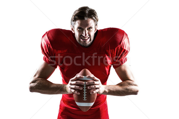 Aggressive American football player in red jersey holding ball Stock photo © wavebreak_media
