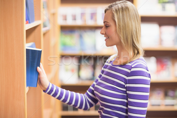 Young woman selecting book from bookshelf in library Stock photo © wavebreak_media