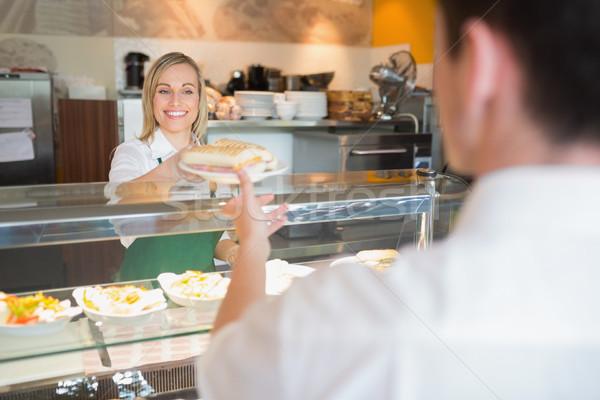 Female shop owner giving sandwich to customer Stock photo © wavebreak_media