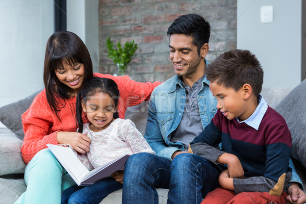 Happy young family reading a book together Stock photo © wavebreak_media