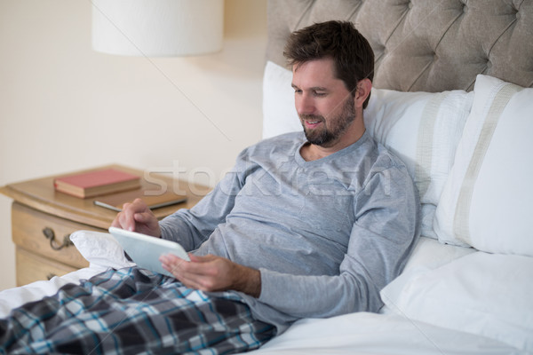 Man using digital tablet in bed Stock photo © wavebreak_media