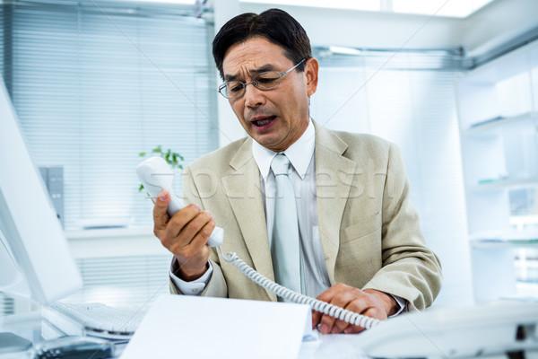 Frustrated businessman looks his phone Stock photo © wavebreak_media