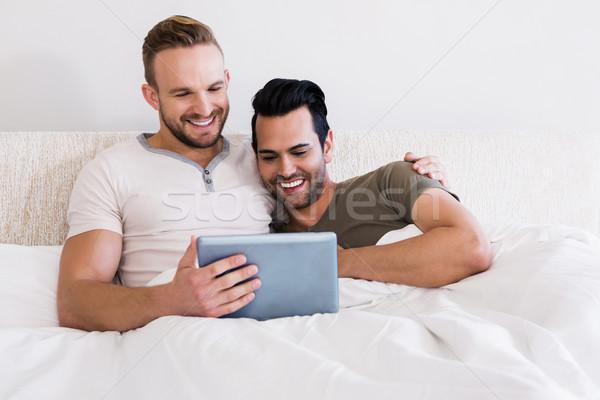 Happy gay couple using tablet Stock photo © wavebreak_media
