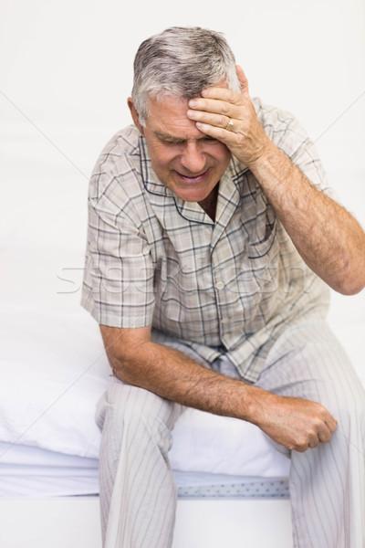 Stock photo: Suffering senior man touching his forehead