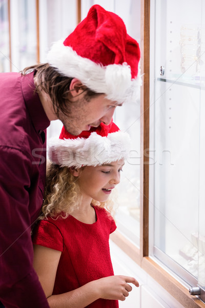 Father and daughter in Christmas attire looking at jewelry displ Stock photo © wavebreak_media
