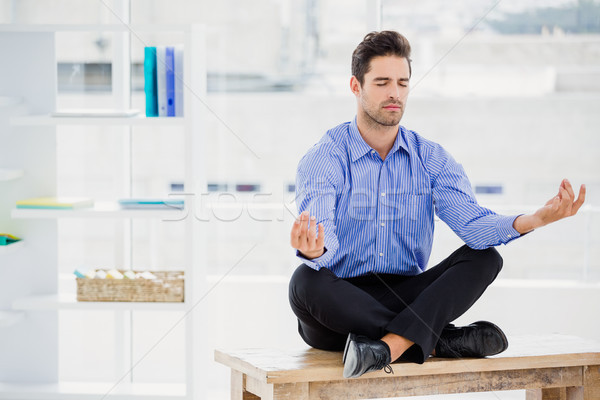 Businessman meditating in lotus pose Stock photo © wavebreak_media