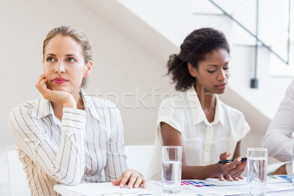 Businesswoman day dreaming while having meeting with colleagues Stock photo © wavebreak_media