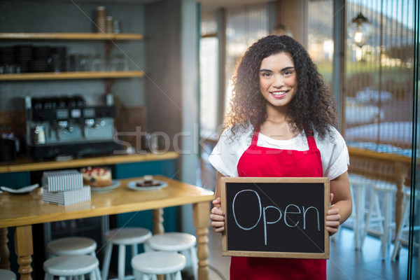 Smiling waitress showing slate with open sign Stock photo © wavebreak_media