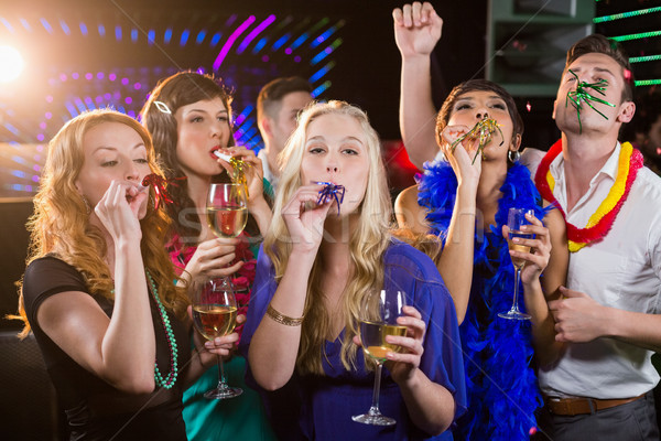 Group of friends blowing party horn in bar Stock photo © wavebreak_media