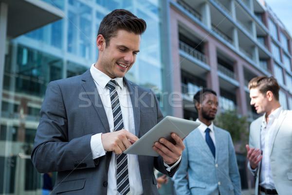 Empresário digital comprimido prédio comercial sorridente internet Foto stock © wavebreak_media