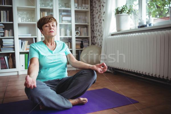 Senior mulher meditando lótus posição casa Foto stock © wavebreak_media