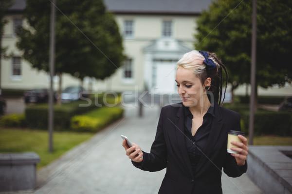 女性実業家 携帯電話 使い捨て コーヒーカップ オフィス ストックフォト © wavebreak_media