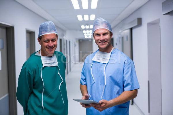 Portrait of surgeon and nurse standing in corridor Stock photo © wavebreak_media