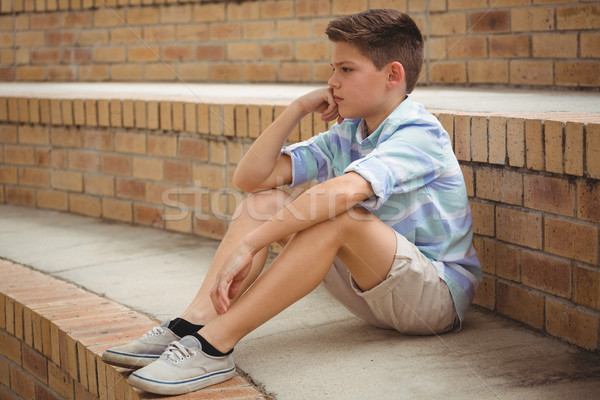 Sad schoolboy sitting alone on steps in campus Stock photo © wavebreak_media
