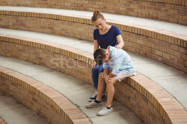 Schoolgirl consoling her sad friend on steps in campus Stock photo © wavebreak_media