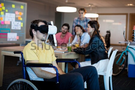 Stock photo: Physically disabled man on wheelchair using VR headset