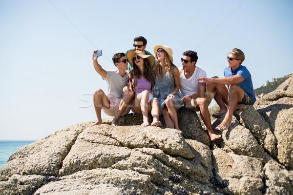 Arkadaşlar oturma kaya kadın plaj Stok fotoğraf © wavebreak_media