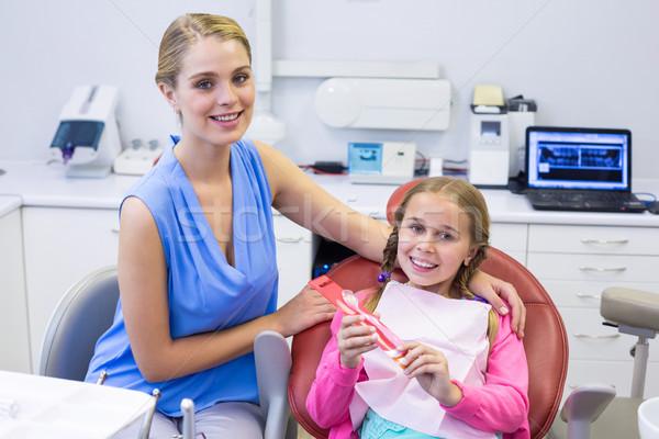 Сток-фото: улыбаясь · матери · дочь · стоматологических · клинике · женщину