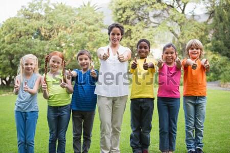 Cute pupils posing on the grass outside  Stock photo © wavebreak_media