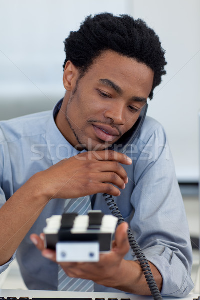Young businessman on phone looking at card holder Stock photo © wavebreak_media