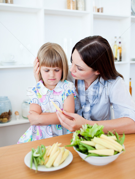 Dissatisfied blond girl eating vegetables with her mother Stock photo © wavebreak_media