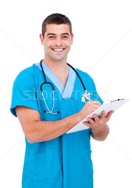 Self-assured male doctor making notes in a patient's folder  Stock photo © wavebreak_media