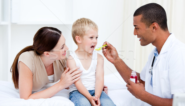 Mixed-race doctor giving some syrup to the little boy  Stock photo © wavebreak_media