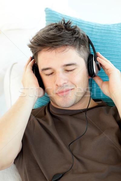 Attrattivo giovane ascoltare musica divano cuffie rock Foto d'archivio © wavebreak_media