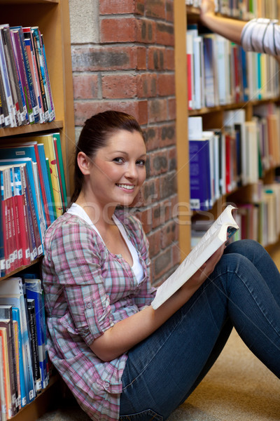 Smiling young woman reading a book sitting on the floor in a bookstore Stock photo © wavebreak_media