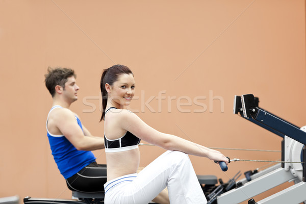 Positive woman with her boyfriend using a rower in a sport centre Stock photo © wavebreak_media
