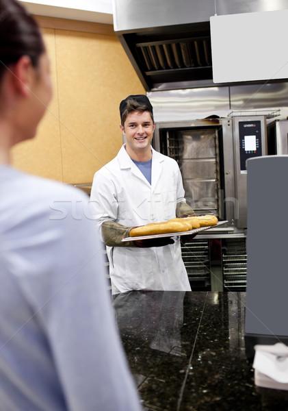 Vrolijk bakker tonen baguettes vrouwelijke klant Stockfoto © wavebreak_media