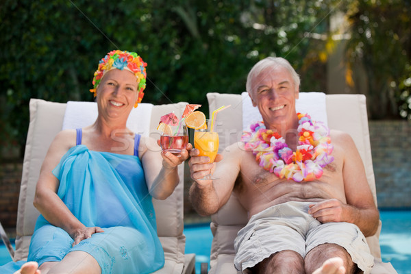 Mature couple drinking a cocktail  beside the swimming pool at home Stock photo © wavebreak_media