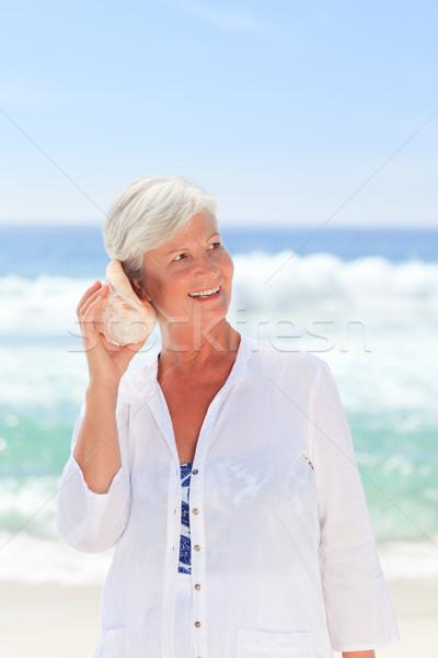 Olgun kadın dinleme kabuk gülümseme spor deniz Stok fotoğraf © wavebreak_media