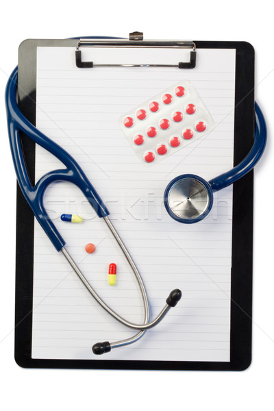Note pad and stethoscope with color pills and blister strip on a white background Stock photo © wavebreak_media