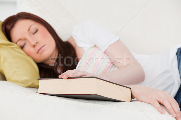 Good looking red-haired girl having a rest while studying on a sofa in the living room Stock photo © wavebreak_media