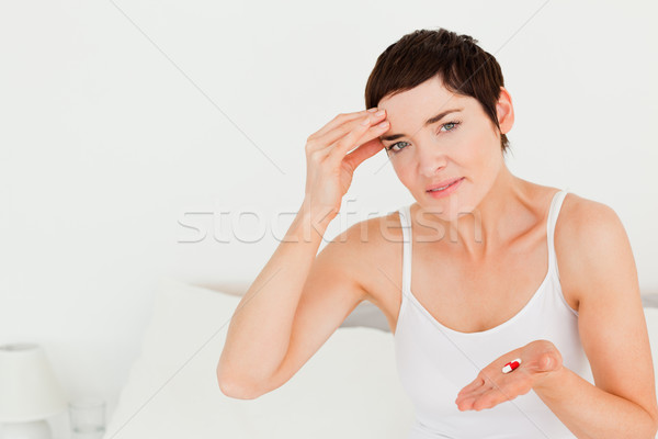 Brunette having a headache in her bedroom Stock photo © wavebreak_media