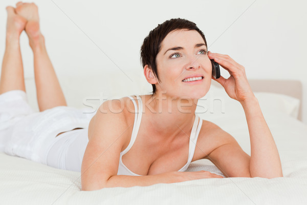 Cute woman calling while lying on her bed looking away from the camera Stock photo © wavebreak_media