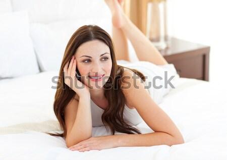 goodlooking woman lying on bed with crossed legs looking into camera in bedroom Stock photo © wavebreak_media