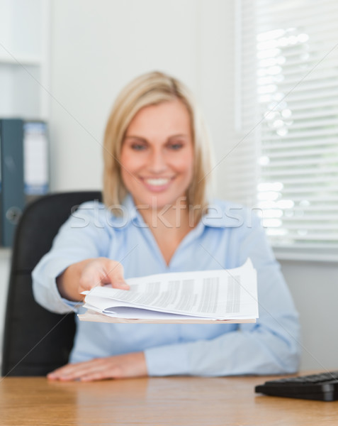 Smiling blonde businesswoman passing a paper looking at it in her office Stock photo © wavebreak_media