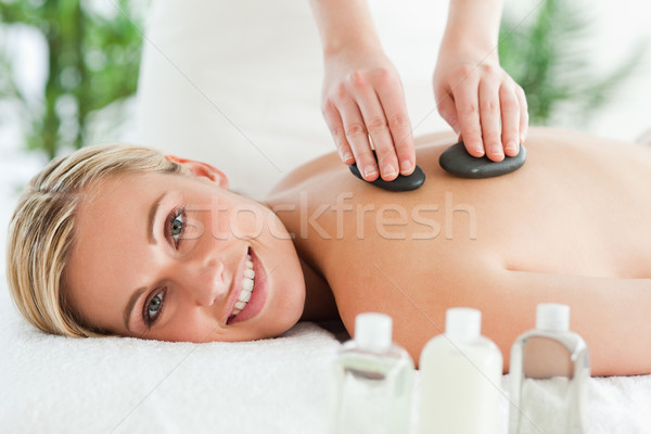 Blonde smiling woman experiencing a stone therapy in a wellness center Stock photo © wavebreak_media