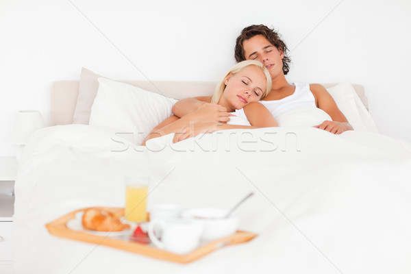 Sleeping couple with the breakfast put on a tray with the camera focus on the models Stock photo © wavebreak_media