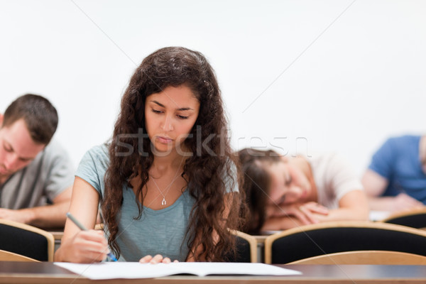 Students writing while their classmate is sleeping in an amphitheater Stock photo © wavebreak_media