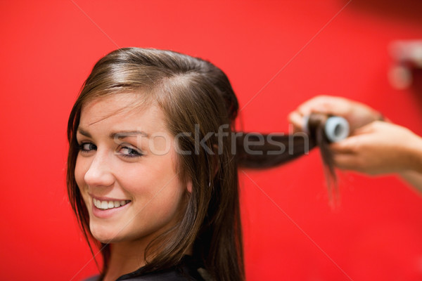 Smiling woman having her hair rolled with a curler Stock photo © wavebreak_media