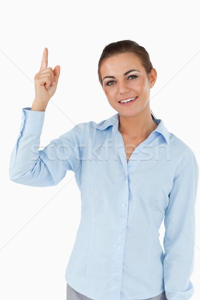 Smiling businesswoman pointing upwards against a white background Stock photo © wavebreak_media