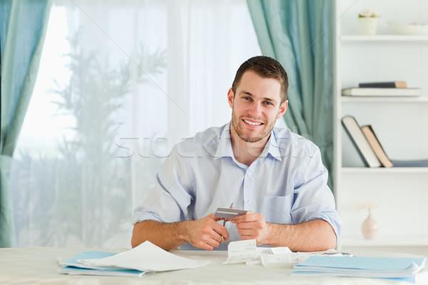 Stock photo: Young businessman solving his problems by destroying his credit card