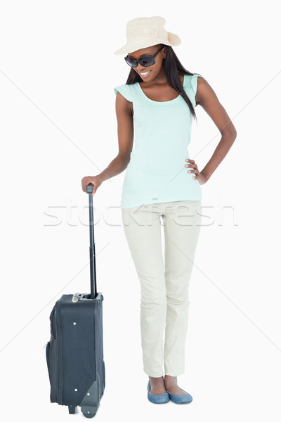Smiling young woman looking at her suitcase against a white background Stock photo © wavebreak_media