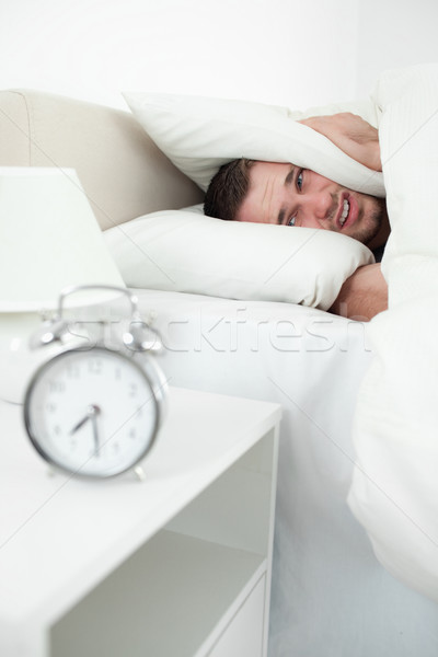 Portrait of a unhappy man covering his ears with a pillow while his alarm clock is ringing Stock photo © wavebreak_media
