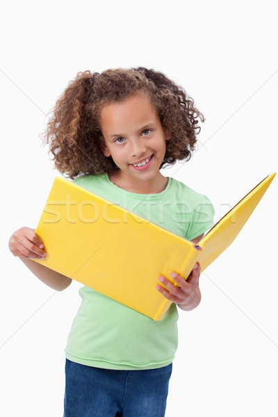 Stock photo: Portrait of a smiling girl reading a fairy tale against a white background