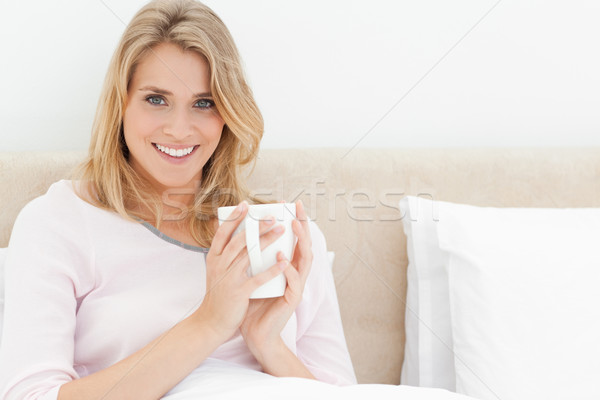 A woman sitting upright in bed, with a cup in her hands held in front of her as she looks ahead smil Stock photo © wavebreak_media