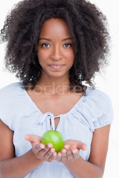 Young curly woman holding a green apple in her hands against a white background Stock photo © wavebreak_media